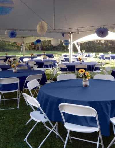 Round tables with navy linens and white chairs