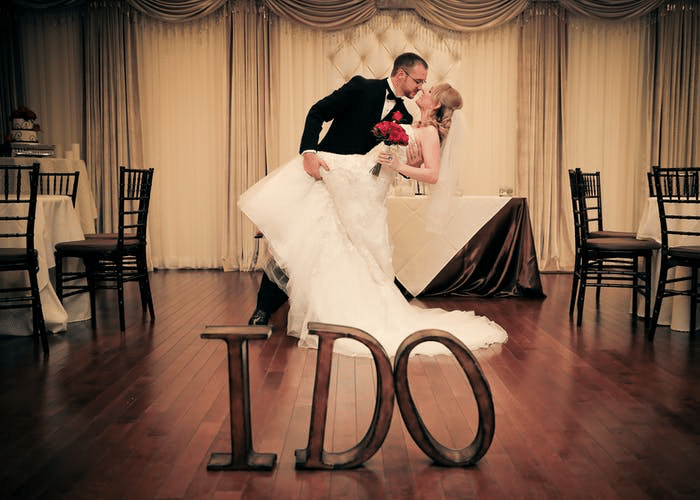 Wedding couple dancing at party on dance floor around tables, chairs and linens