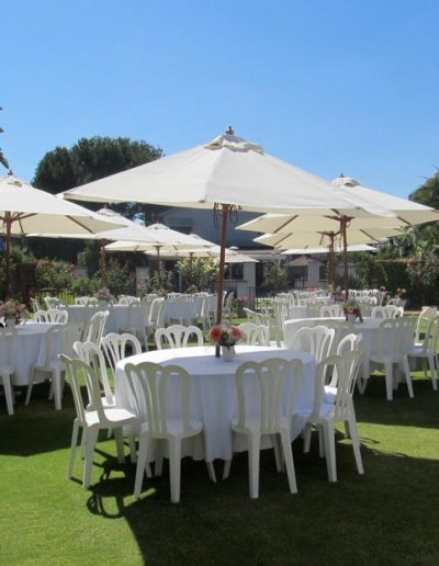 white Cafe chairs, linens , tables and white umbrellas at party